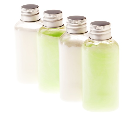 Four small transparent plastic bottles filled with cosmetic pastel-green and white lotion and sealed with a silver metal cap. The green contents of the bottle can be lotion, shampoo, conditioner, liquid soap, shower gel etc. Isolated on white background. photo