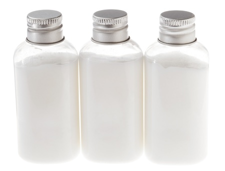 Three small transparent plastic bottles filled with white cosmetic cream and sealed with a silver metal cap. The white contents of the bottle can be lotion, shampoo, conditioner, liquid soap, shower gel etc.