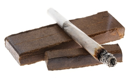 A lit joint laid on two pieces of Hashish (about 30 grams), isolated on white background.