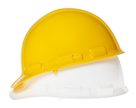 Side view of two hard hats, yellow on top of white, isolated on white background. photo