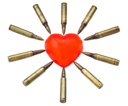 desease: A heart shaped bar of soap is surrounded by 5.56 cartridges pointing at it. Fits the concept of Heart Attack. Isolated on white background