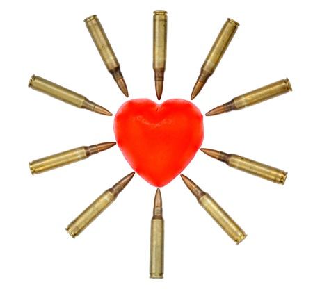 A heart shaped bar of soap is surrounded by 5.56 cartridges pointing at it. Fits the concept of 'Heart Attack'. Isolated on white background Stock Photo - 18907250