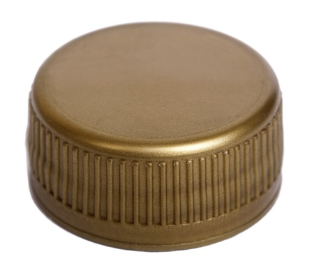 Slightly high angle view of a golden plastic bottle cap isolated on white background. Top side.