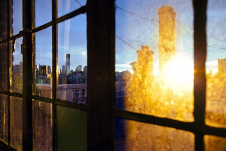 freedom tower: One World Trade Center (aka Freedom Tower) and Lower Manhattan skyline seen through defocused window back lit by afternoon yellow sun on a rooftop West Village apartment. Stock Photo
