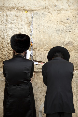 Jerusalem, Israel - May, 21st 2010  Two Jewish orthodox men, pressed in prayer against the wailing wall, the holiest site in Judaism; located in the old city of Jerusalem