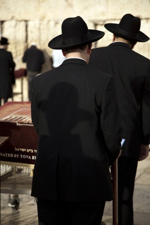 Orthodox Jewish men praying in front of the sacred Wailing Wall, located at the old city of Jerusalem, Israel