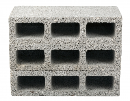 Three gray concrete construction blocks (a.k.a. cinder block, breeze block, cement block, foundation block, besser block; professional term: Concrete Masonary Unit - CMU) in a straight stack, isolated on white background. Stock Photo