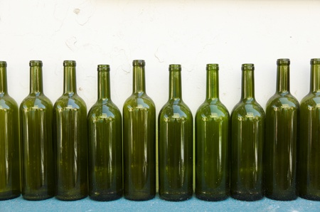ten empty: Ten empty green wine bottles in a row on the background of old run-down white wall, resting on turquoise wooden surface. Stock Photo