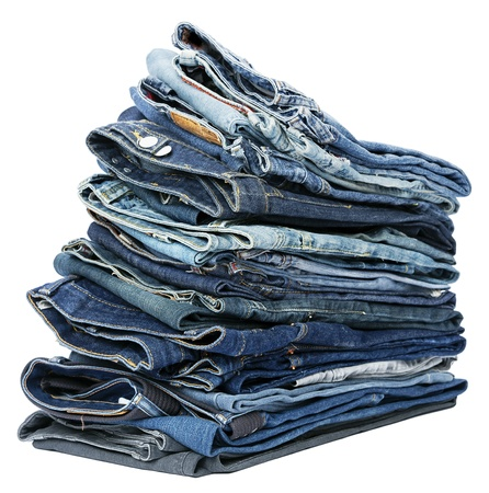 A stack of various pairs of jeans pants isolated on white background. Stock Photo