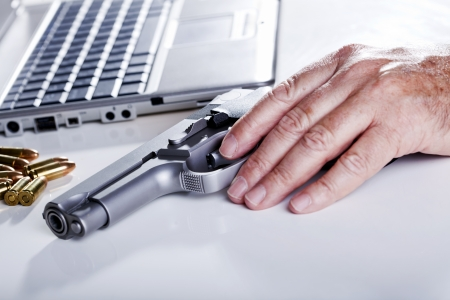 The left hand of a mature adult man resting on a 9mm handgun. 9mm bullets are scattered in the background as well as a laptop computer. photo