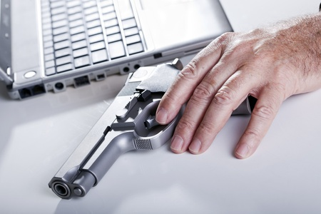 The left hand of a mature adult man resting on a 9mm handgun, and a defocused laptop computer in the background. Backlit. photo