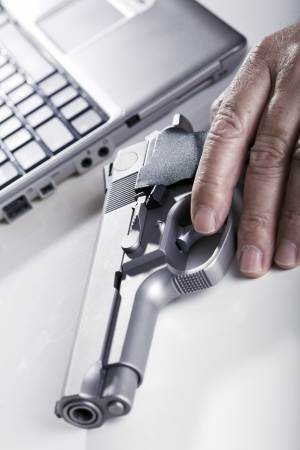 backlit keyboard: The left hand of a mature adult man resting on a 9mm handgun, and a defocused laptop computer in the background. Backlit. Shallow depth of field - focus on the trigger.