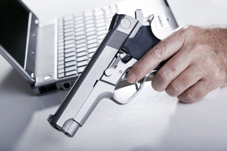 The left hand of a mature adult man holding a 9mm handgun, and a defocused laptop computer in the background. Backlit. Shallow depth of field. photo