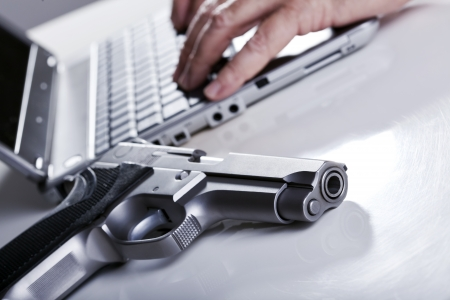 backlit keyboard: A 9mm handgun resting on a table, and defocused in the background the hands of a mature adulat man are typing on the keyboard of a laptop computer. Backlit, shallow depth of field - focus on the gun barrel.