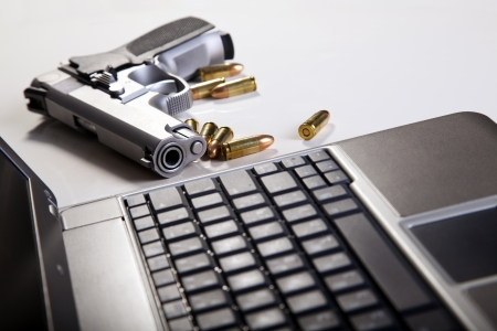 gun barrel: A 9mm handgun with scattered bullets beside it and part of a laptop computer. Backlit, shallow depth of field.