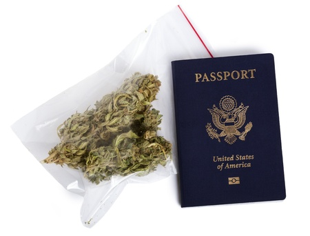 A USA passport and a zip-lock plastic bag containing marijuna buds isolated on white background. photo