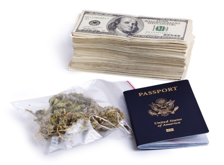 A USA passport, a zip-lock plastic bag containing marijuna buds and a large stack of 100 US dollar money notes isolated on white background. photo