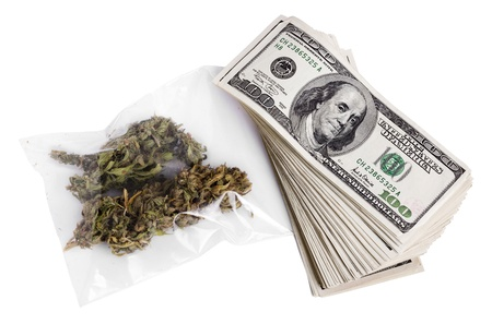 A zip-lock plastic bag containing marijuna buds and a large stack of 100 US dollar money notes isolated on white background.