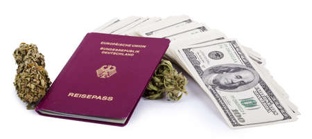 A German passport, two Marijuana buds and a large stack of 100 US dollar money notes isolated on white background. photo