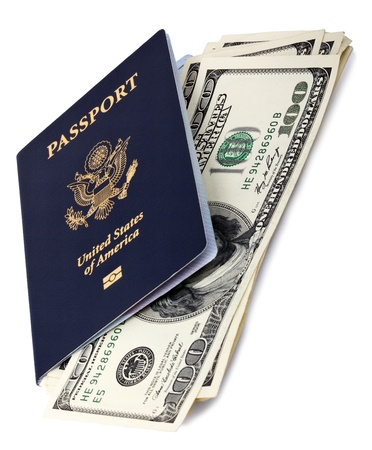 A USA passport (with the biometric chip) with several 100 US$ money notes peeping out from within it. Isolated on white background. photo