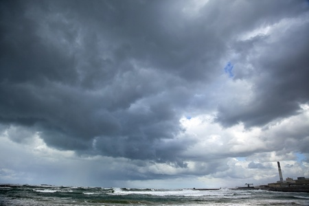 Heavy gray rain clouds and a gushing green sea at a stormy winter day. Shot in Tel-Aviv port, the