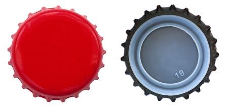 gorra: Ambos lados de una tapa de botella de metal rojo. Una de la parte superior y uno de la parte inferior. Aislado sobre fondo blanco.