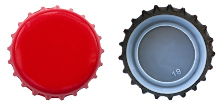 nonalcoholic beer: Both sides of a red metal bottle cap. One of the top side and one of the bottom side. Isolated on white background. Stock Photo