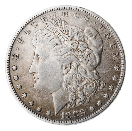 minted: Frontal view of the obverse (heads) side of a silver dollar minted in 1883, known by the name Morgan Dollar (named after its designer). Depicted is a profile portrait representing liberty. Isolated on white background.
