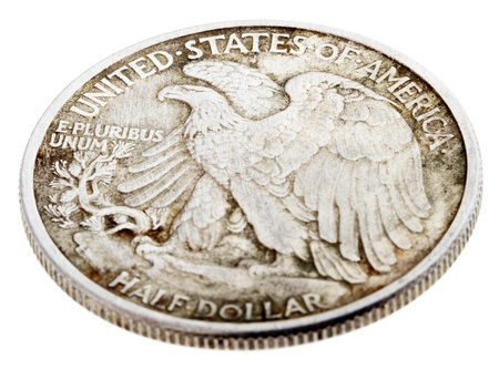 american silver eagle: High angle view of the reverse (tails) side of a silver half Dollar minted in 1942. Depicted is a bald eagle rising from a mountaintop perch. Isolated on white background.