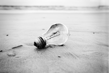inclement weather: A used burnt-out incandescent light bulb abandoned on a sandy beach in inclement weather. Relates to energy conservation and environmental issues in general.