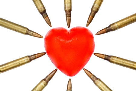 under arrest: A heart shaped bar of soap is surrounded by 5.56 cartridges pointing at it. Fits the concept of Heart Attack. Isolated on white background