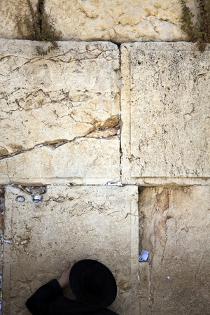 An orthodox Jewish senior man pressed in prayer against the wailing wall in the old city of Jerusalem. photo