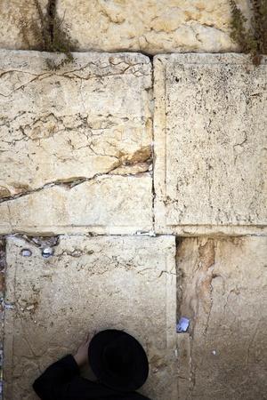 Ortodoksyjnych Żydów starszy człowiek wciśnięty w modlitwie przed Ścianą Płaczu w starym mieście w Jerozolimie.