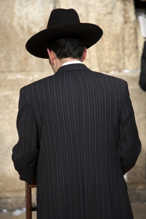 An orthodox Jewish young adult man praying in front of the wailing wall in the old city of Jerusalem, Israel. photo