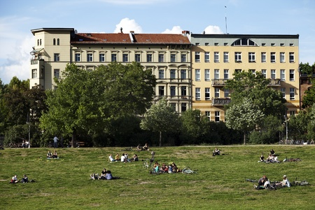 east berlin: Berlin, Germany - June 8th, 2012: Groups of young adults and teenagers scattered on the grass at Gorlitzer park, located in Kreuzberg, East Berlin, Germany; on a lovely sunny spring day. Editorial