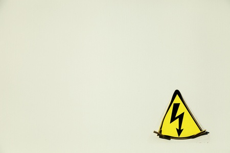 electrify: Old electric hazard sticker starting to peel off of the bright beige metal surface on which it