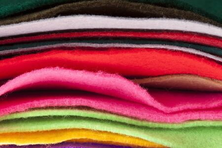 Felt fabric sheets in various colors piled up in a stack. photo