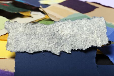 Torn long white rice fiber paper on the background of a large group of torn pieces of paper in a variety of colors. Good as copy space for text. photo