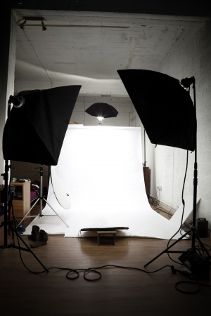 Loft turned into a photographer studio ready for action. White paper limbo surrounded by lighting equipment.