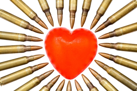 A heart shaped bar of soap is surrounded by 5.56 cartridges pointing at it. Fits the concept of 'Heart Attack'. Isolated on white background Stock Photo - 18982737