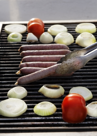 apparently: Sausages, onion slices and tomato getting ready on an outdoor barbecue grill. One of the sausages is apparently ready, as tongs are lifting it off of the grill.