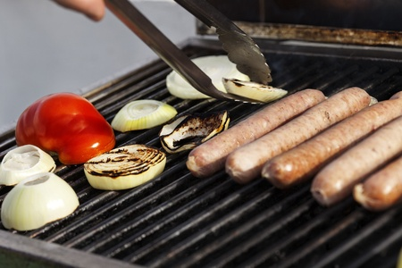 grill tongs sausage: Sausages, onion slices and tomato getting ready on an outdoor barbecue grill. One of the onion slices is being lifted off of the gril with tongs.