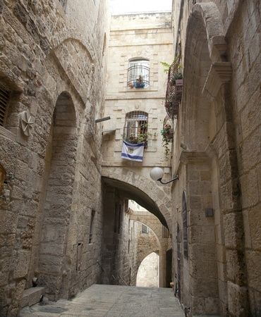 An alley in the Jewish quarter of the old city of Jerusalem, Israel. Hanging from the bottom window is an israel flag with the symbol of Jerusalem instead of the star of David. photo
