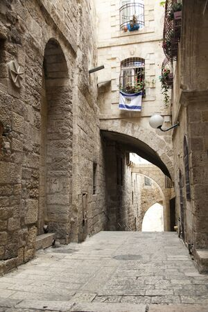 jewish quarter: An alley in the Jewish quarter of the old city of Jerusalem, Israel. Hanging from the bottom window is an israel flag with the symbol of Jerusalem instead of the star of David.