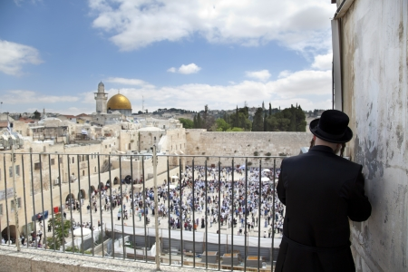 An orthodox religious Jewish man standing on a porch infront of the Western Wall in Jerusalem and praying. photo