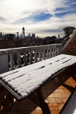freedom tower: Snow covered picnic table on a West Village rooftop porch, with downtown Manhattan skyline in the background (and the almost ready Freedom Tower) Stock Photo