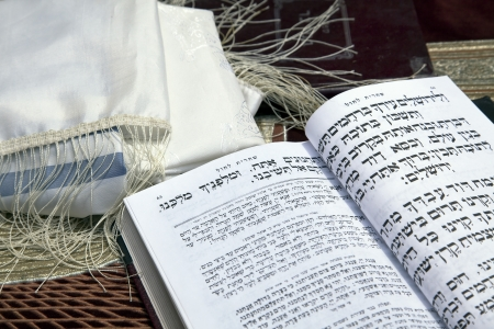 A Jewish praying shawil and a Jewish prayer book opened on one of the pages of the morning prayer, resting on a velvet tablecloth with an image of the Jewish temple from 2000 years ago. Shot in the western wall in the old city of Jerusalem. photo