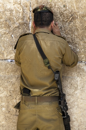 A lieutenant in the Israeli army pressed in prayer against the wailing wall in the old city of Jerusalem  photo