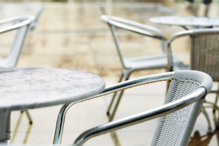 Chairs and table belonging to a cafe remain deserted on a rainy winter day. Stock Photo