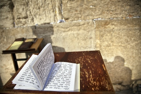 The biblical Book of Psalms opened on one of the pages of the morning prayer, resting on a pedistal . Theres also a shadow of a Jewish orthodox man on the wailing wall in the background. Shot in the western wall in the old city of Jerusalem. Stock Photo
